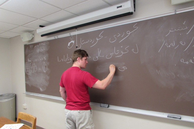 A student writes a foreign language on a chalkboard