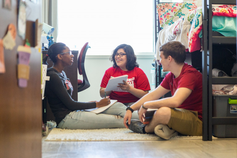 Students talk in a residence hall room
