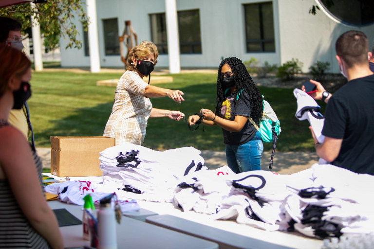 a woman wearing a mask points a masked student to a table of T-shirts