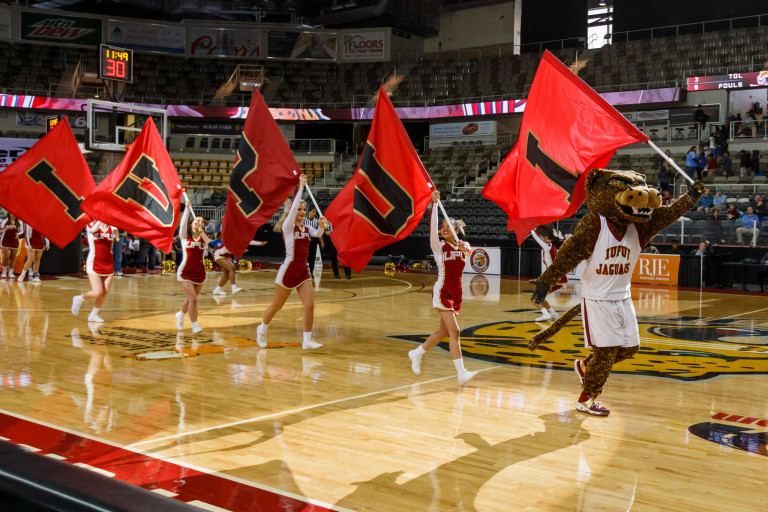 Cheerleaders led by Jawz mascot carry flags that spell out IUPUI on a basketball court
