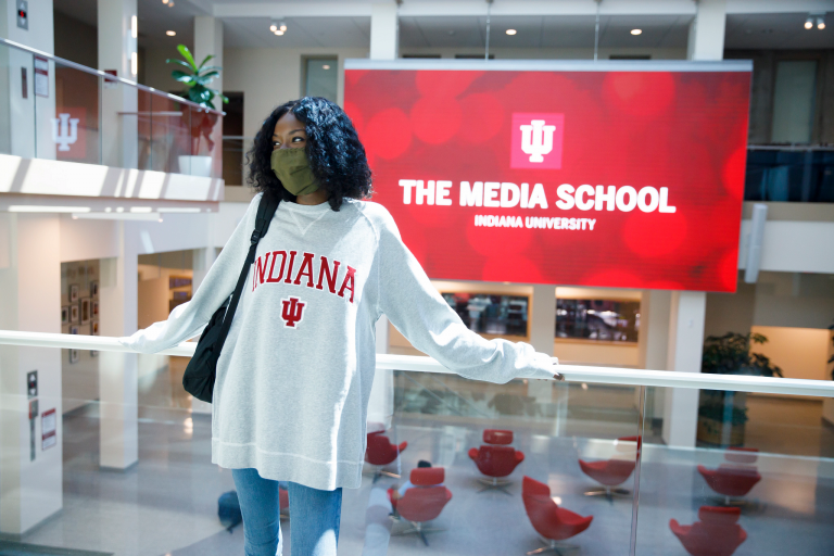 Student standing in front of The Media School sign