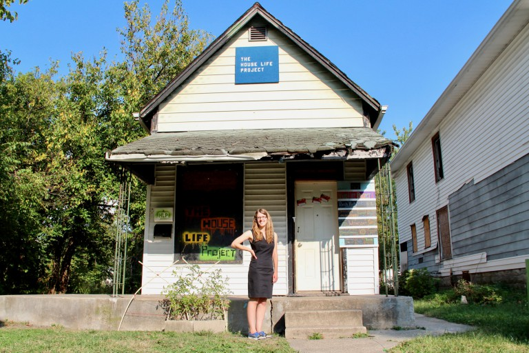 Laura Holzman stands in front of a house.