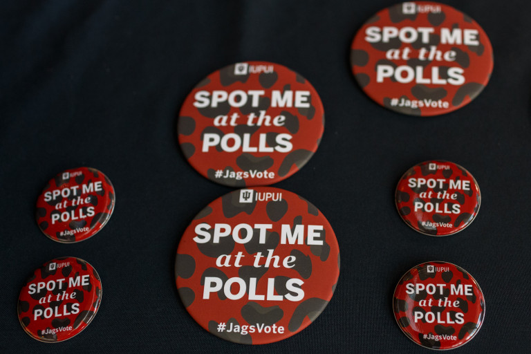 "a close up of buttons that read ""Spot me at the polls"" with an IUPUI logo on them"