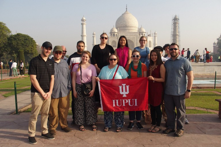 Students abroad holding IUPUI's flag