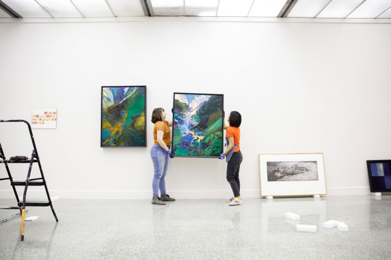 Two people hang a large colorful painting on a wall with other art