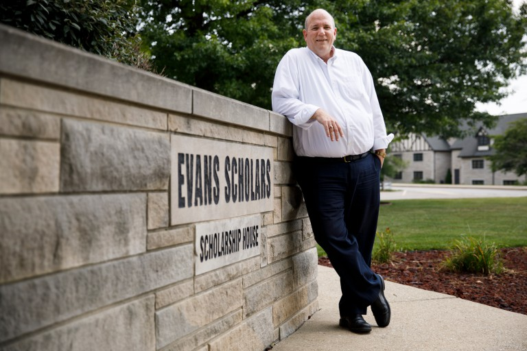 Tom McMahon posing in front of the Evan Scholars sign