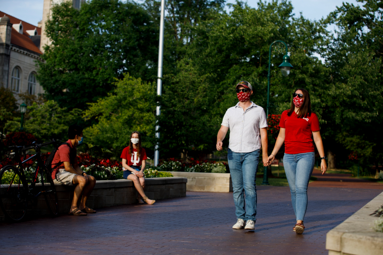 A couple wears masks and holds hands while walking on the IU Bloomington campus