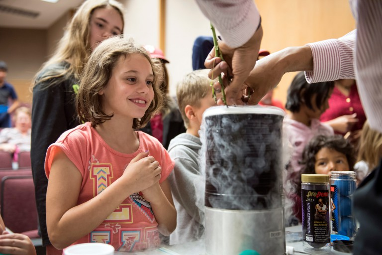 A young girl watches an experiment with liquid nitrogen