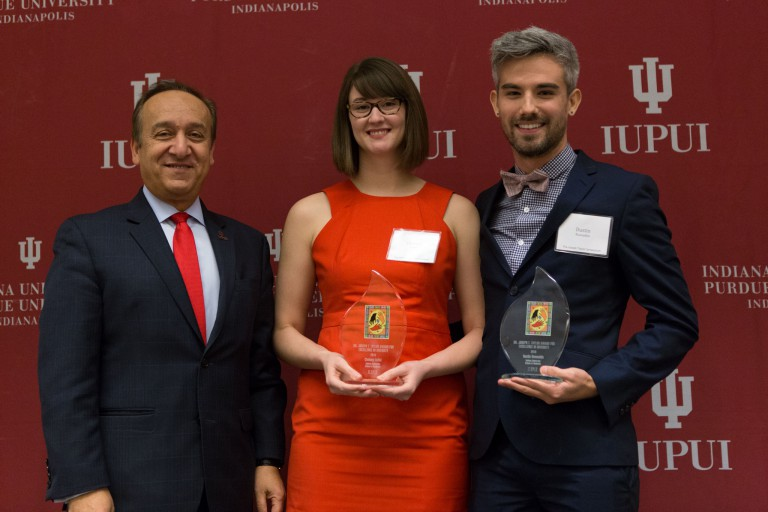 Three people display glass trophies in front of a red backdrop.