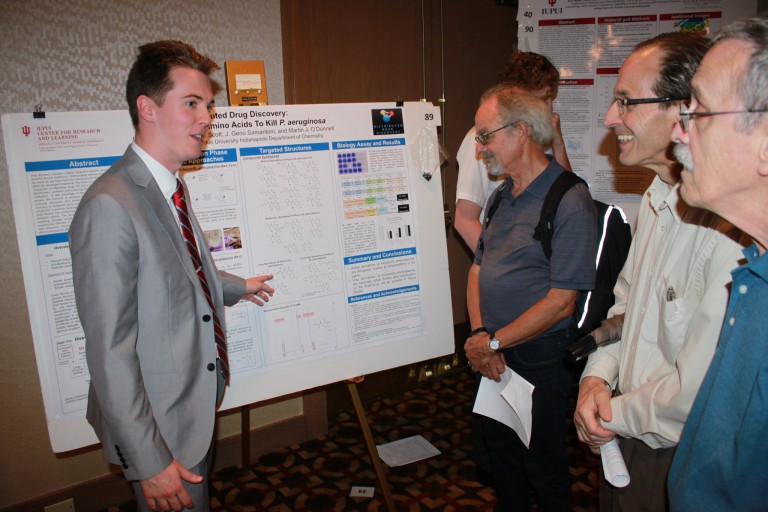 Isaac Lamb points to a large poster while explaining his research to three professors.