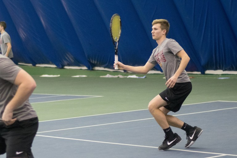 Matt Moe prepares to hit a tennis shot on an indoor court.