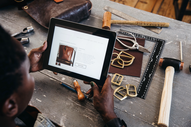 Artisan looks at her online products on a tablet