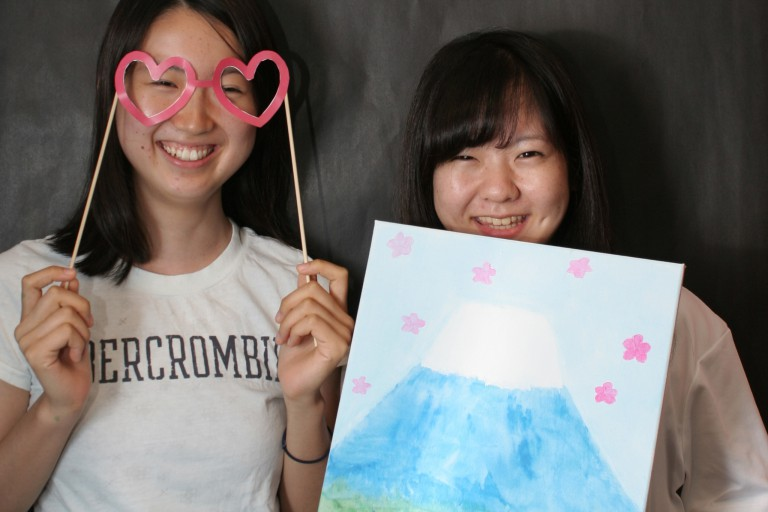 Two International House students pose in a photo booth