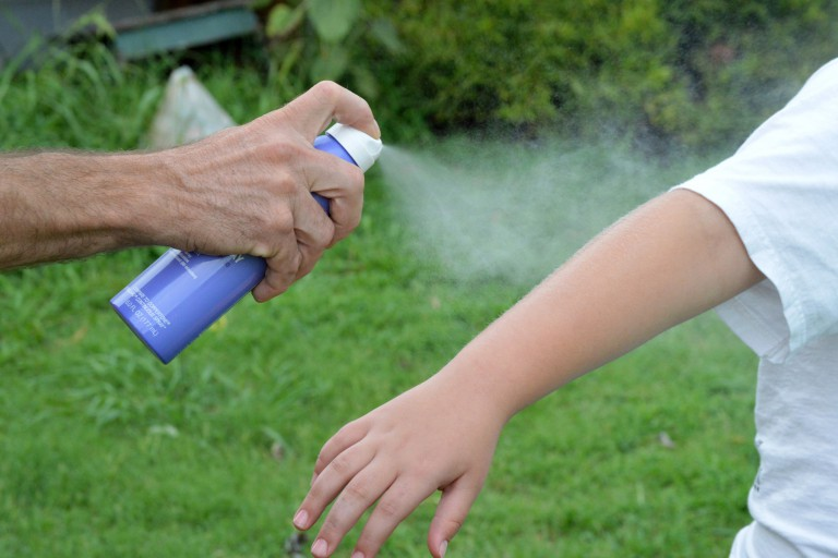 Sunscreen is being sprayed on a child's arm