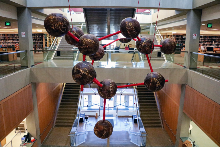 a molecule-like sculpture hangs in the IUPUI University Library
