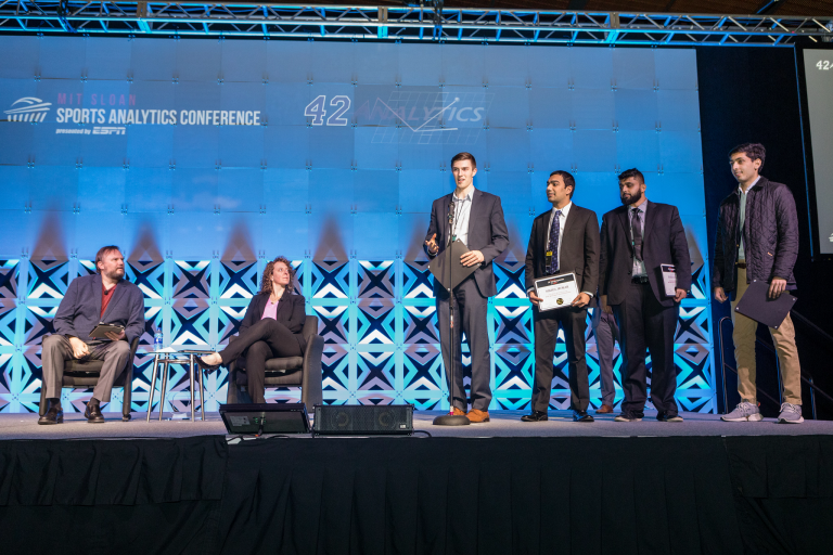 Attendees present onstage at a sports analytics conference
