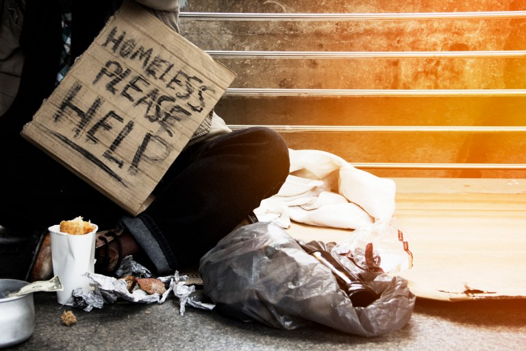 """Photo of someone sitting near the street with a sign that reads """"Homeless please help."""""""