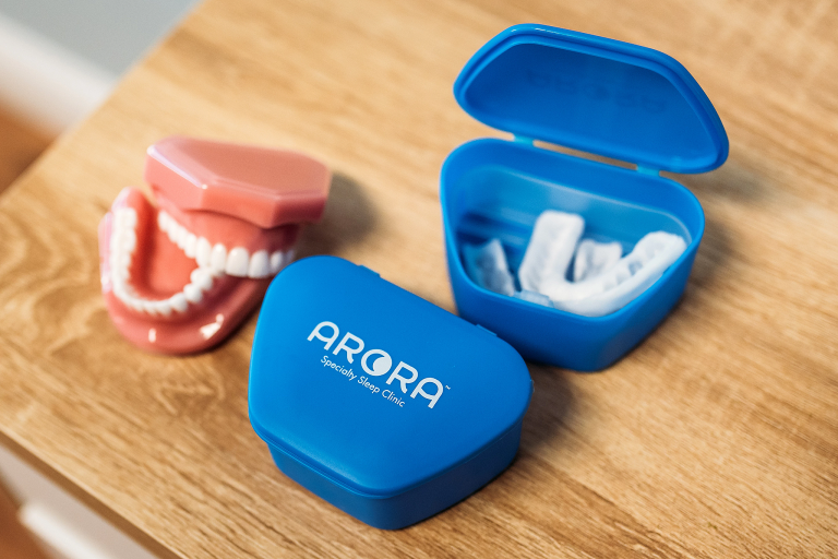 A mouthpiece, storage containers and a set of teeth on a table