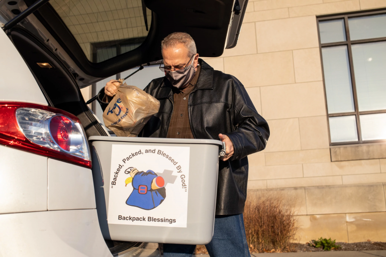 man places packs bags of food in a vehicle for delivery