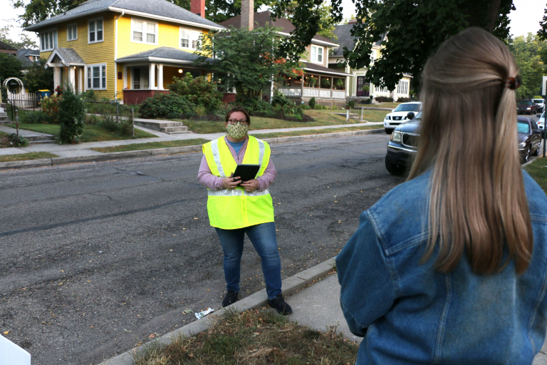 A contact tracer wearing a mask talks to a woman outside on a residential street