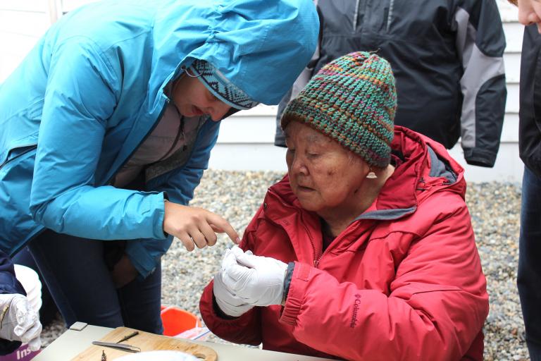 Harriet Penayah examines a stickleback fish