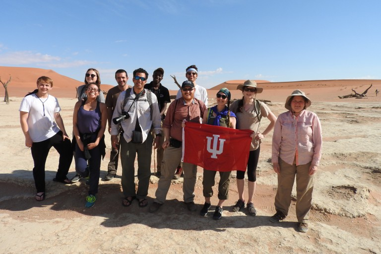 The field biology team poses with the IU flag in the Namib Desert