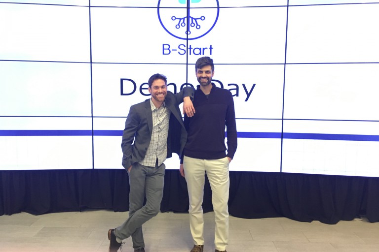 Tom Fennewald and Asaf Beasley of BotMaven stand in front of a screen that reads B-Start Demo Day.