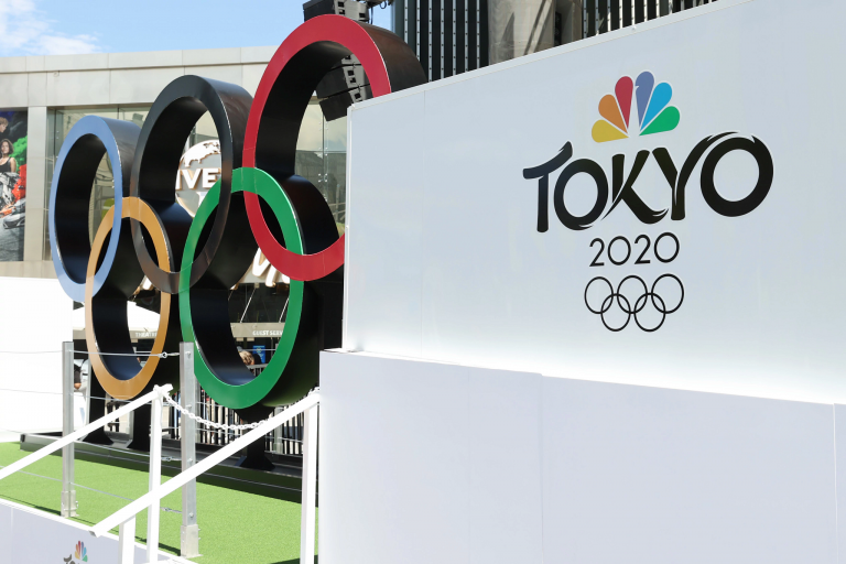 A large-scale Olympics rings statue alongside signage for NBC and Olympics