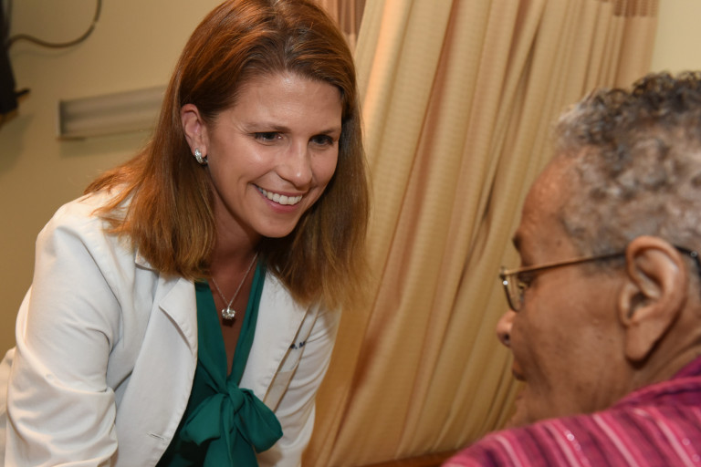 Dr. Kathleen Unroe works with a patient in a hospital room.