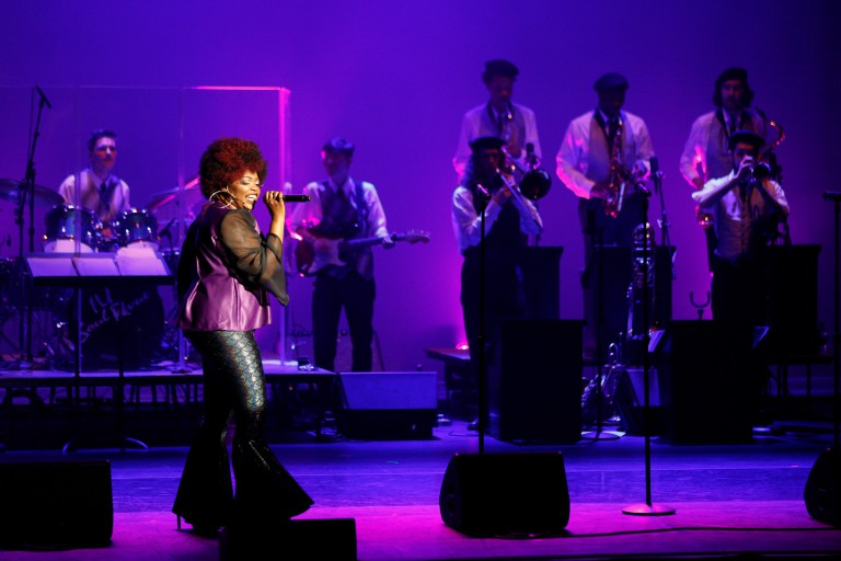 Jasmine Dennie sings on stage during a performance