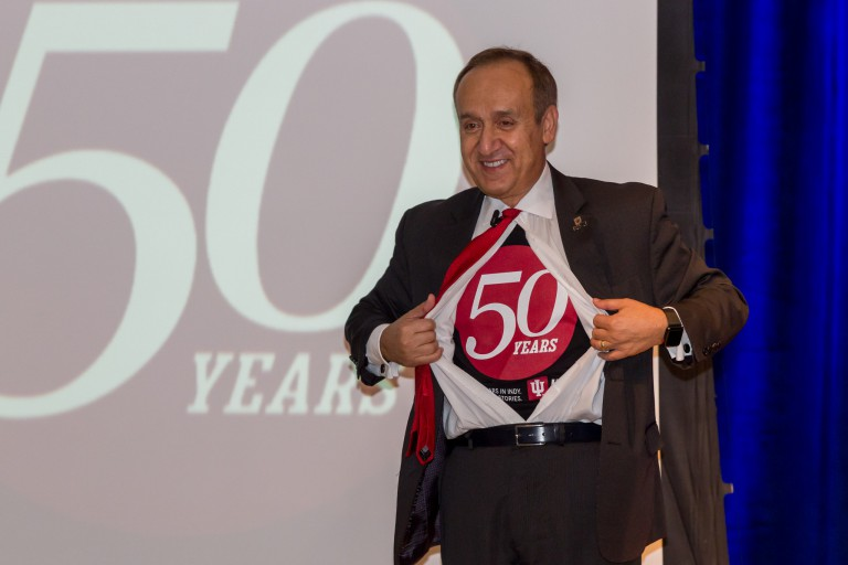 Chancellor Nasser Paydar shows off his 50th-anniversary shirt, Superman style.
