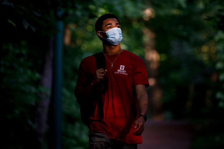 Student walking with a backpack and mask on