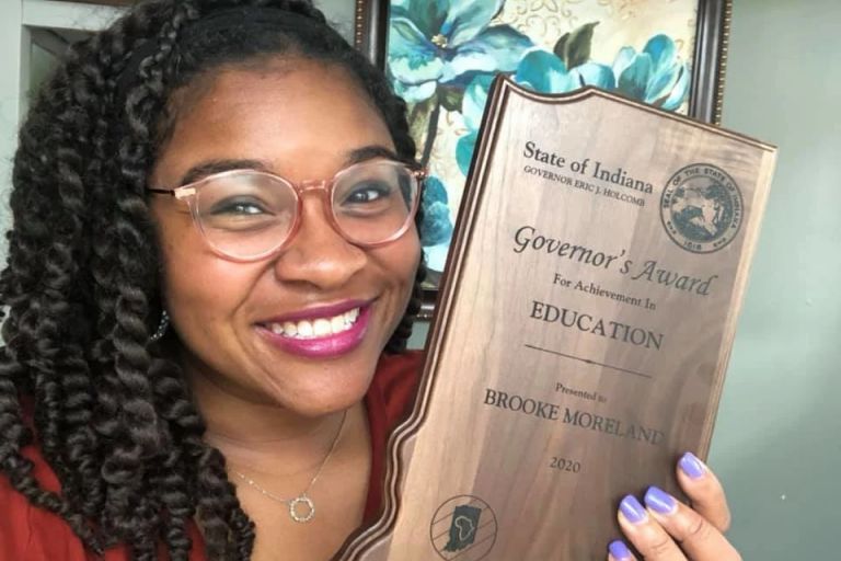 a woman holds up an award