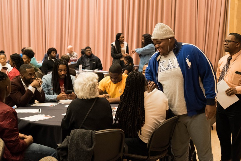 2018 Black History Month event participants visit with each other at round tables, some standing