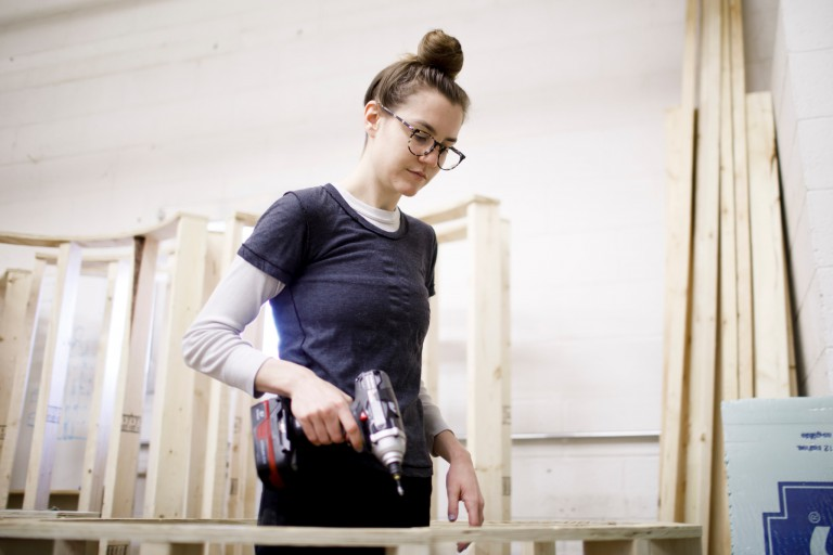 IU student Amanda Waterhouse uses an electric screwdriver to work on her sculpture.