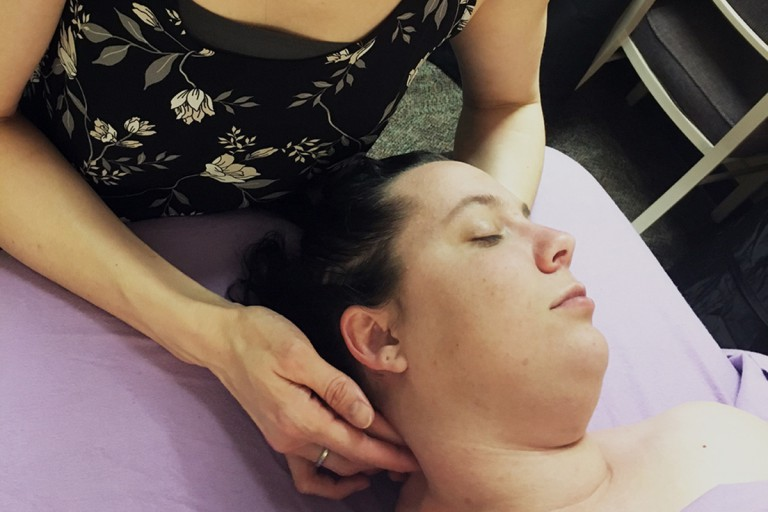 Massage therapist massages back of woman's neck