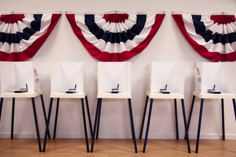 A row of voting booths placed against a wall on which hangs red, white and blue bunting