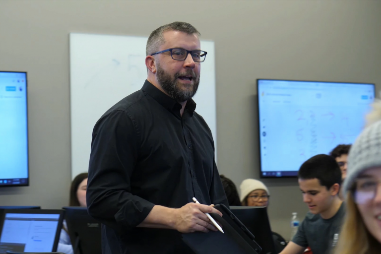 a man in a black dress shirt stands instructing in a classroom