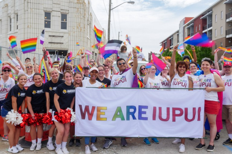 "IUPUI students carry ""We are IUPUI"" banner and pose for a picture during the Indy Pride Parade."