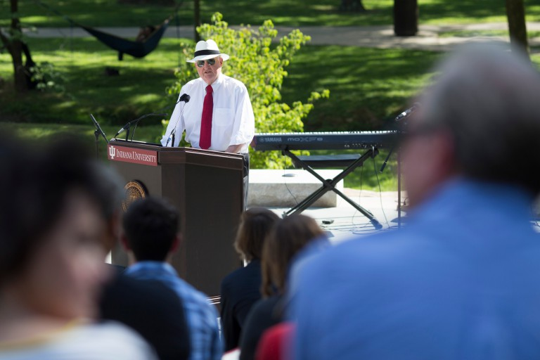 IU President Michael McRobbie stands at a podium on the stage of the Prebys Amphitheater