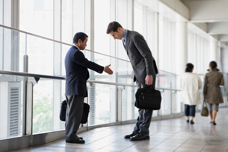 American man bowing while Japanese man holds hand out