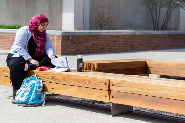 A student studies on a new bench on-campus.