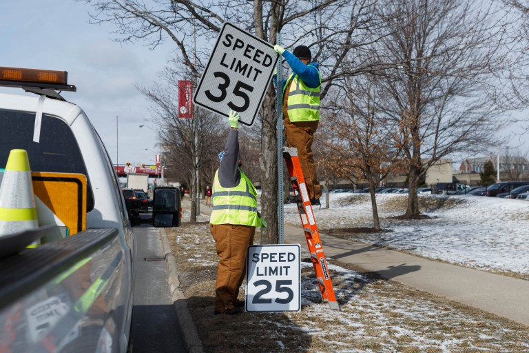 Two city workers change the speed limit signs on Michigan Street