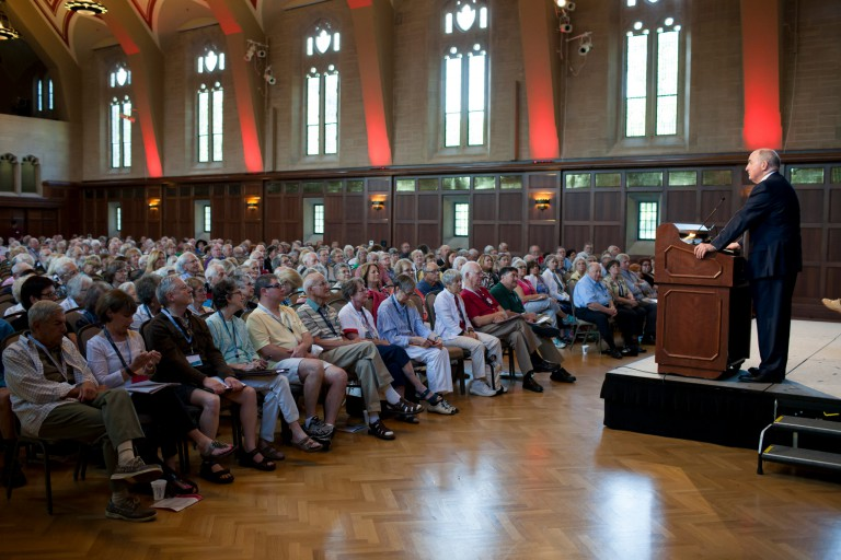 President Michael A. McRobbie stands on a podium to speak to a crowd of attendees in Alumni Hall.