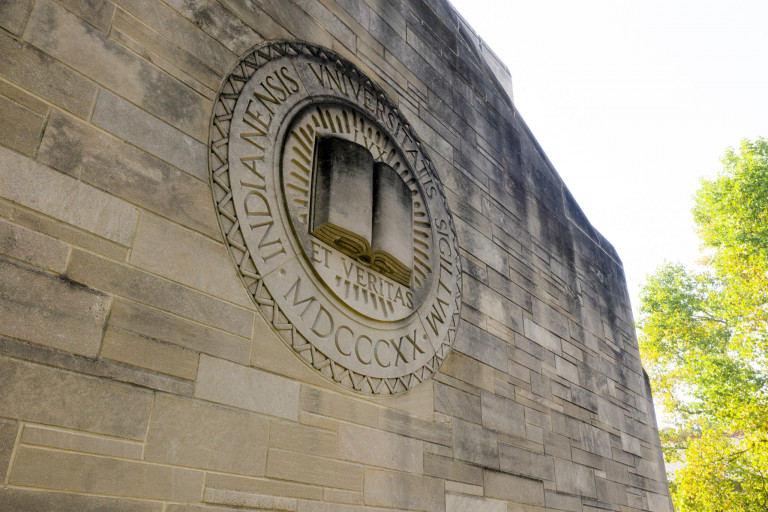 "IU's motto ""Lux et Veritas"" appears on the side of a limestone building."