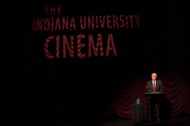 IU President McRobbie speaks before a curtain at IU Cinema