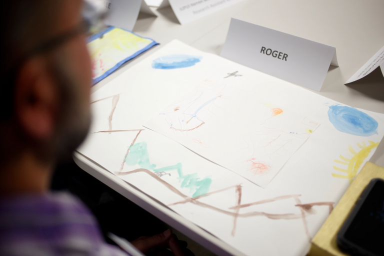 Watercolor art and name tag on a table in front of a person.