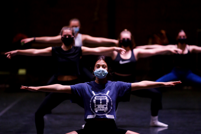 Dancers practice while wearing masks