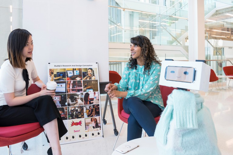 Tingyu Li and Pavithra Ramamurthy relax in chairs with a prototype of their 'Buddy' robot.
