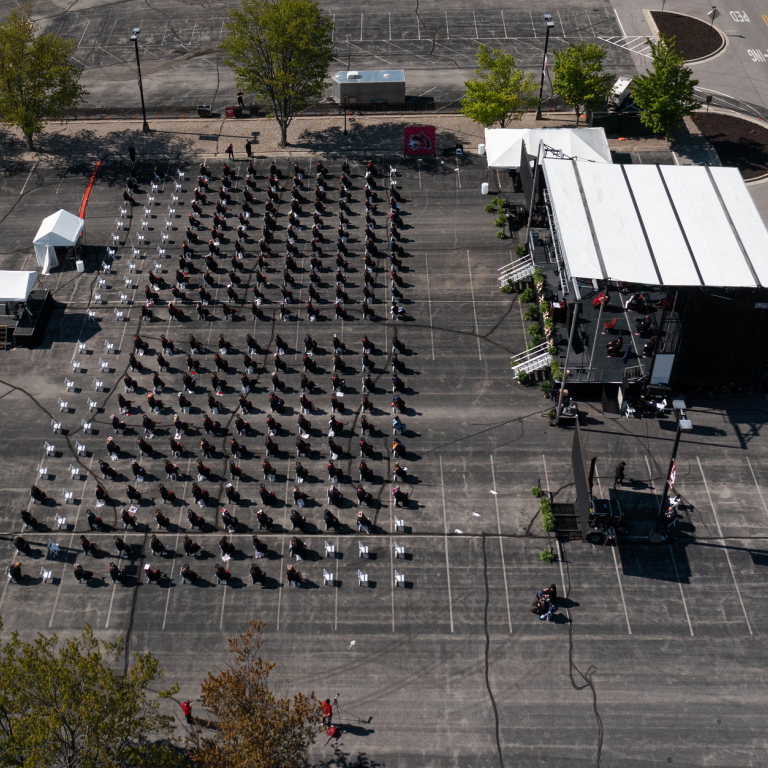 A drone shot from above of graduates seated in rows in a parking lot facing a stage